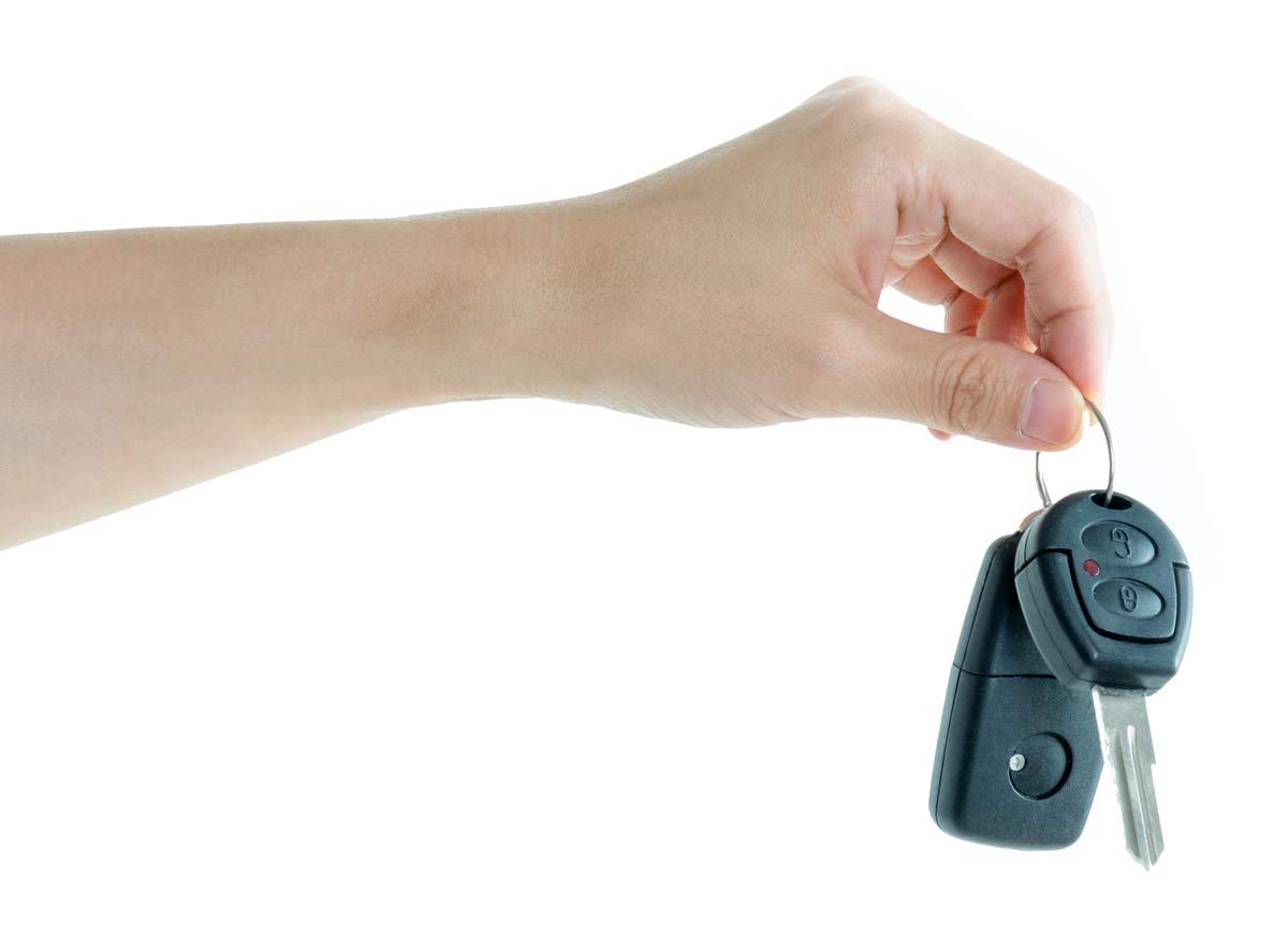 hand holding car keys on white background