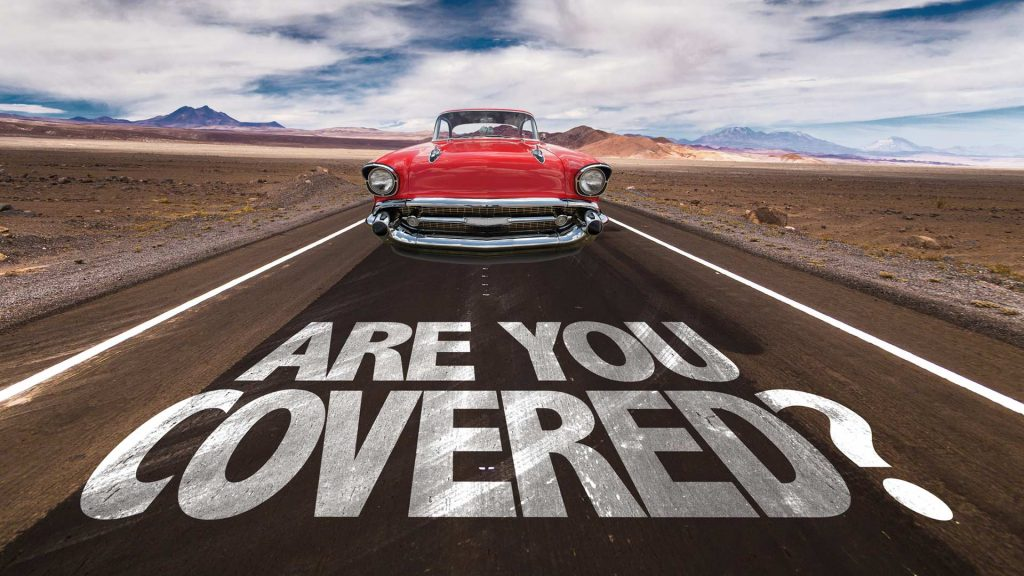 "red classic car driving on road with white text saying ""are you covered?"""